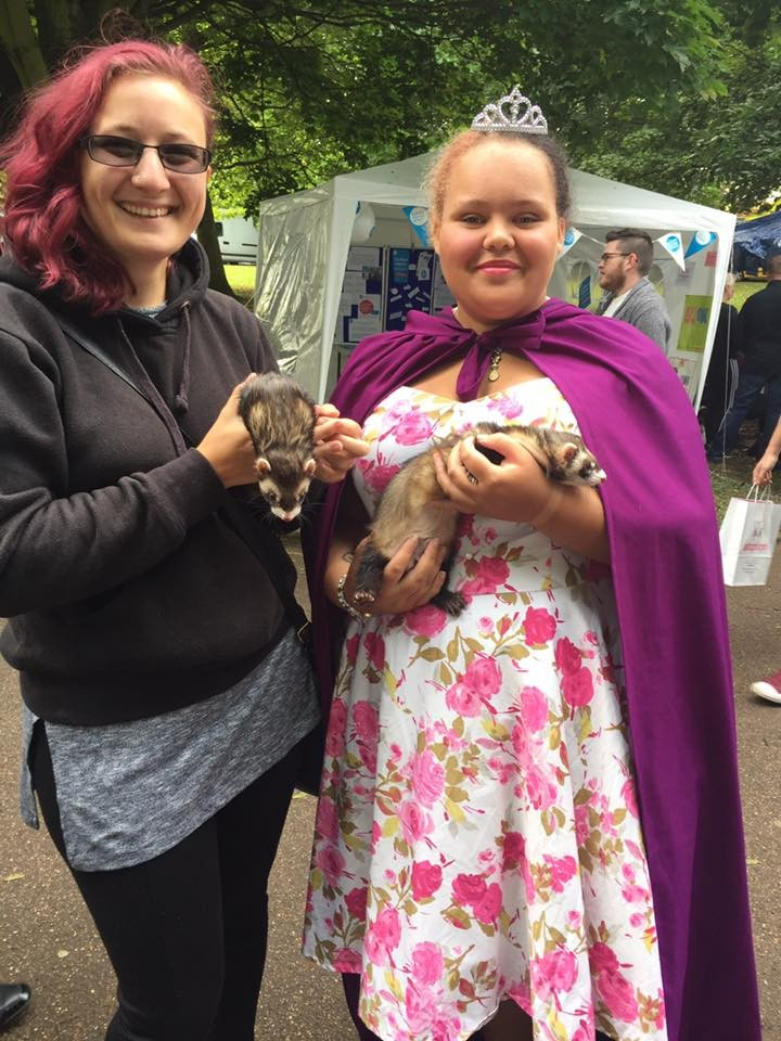Two young ladies one dressed as a princess holding ferrets