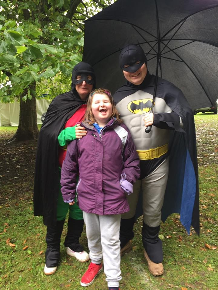 Batman and Robin pose with a young girl in the rain with a umberella